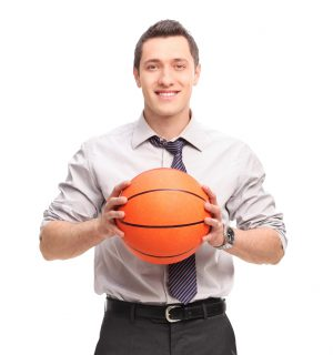 Young businessman holding a basketball and looking at the camera isolated on white background